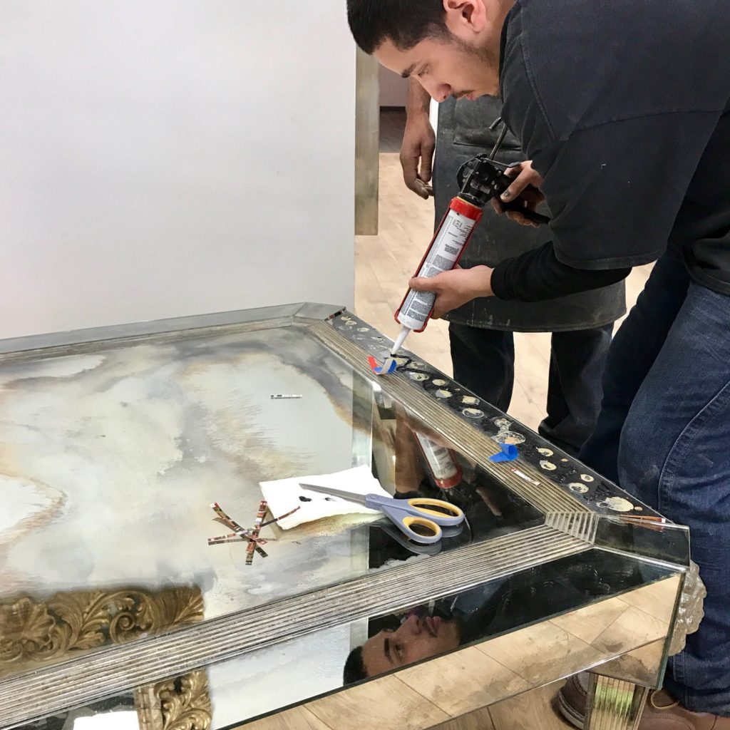 A master glass craftsman repairs an antique mirror coffee table with new mirror made at their workshop